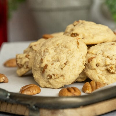 Golden color round molded cookies with chunks of pecans sticking out.