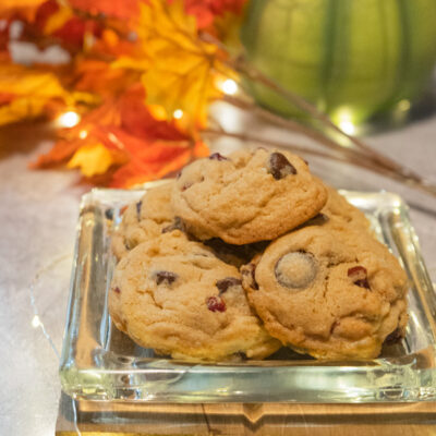 Cranberry and bittersweet chocolate chip cookies on a glass serving dish.
