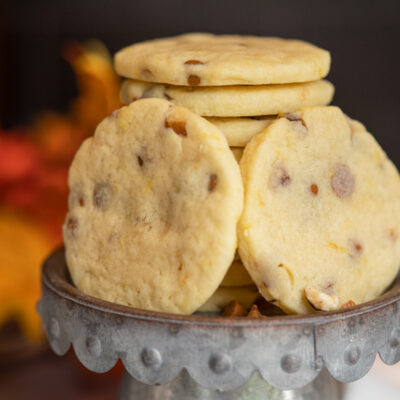 Sugar Cookies with Cinnamon Chips and Orange displayed leaning against a stack of cookies.