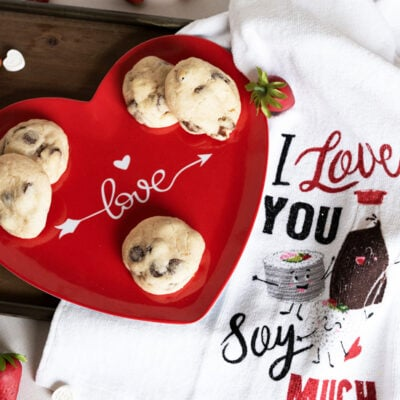 Chocolate Chips and Strawberry Cookies on a heart-shaped plate with a towel.