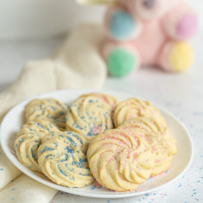Pink and blue sparkling sugar top these round rosette style cookies on a white serving plate.