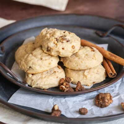 Glazed maple walnut cookies on a metal, old-looking plate with 2 cinnamon sticks.