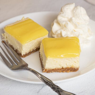 Two pieces of lemon cheesecake with lemon curd with fork and on white plate.