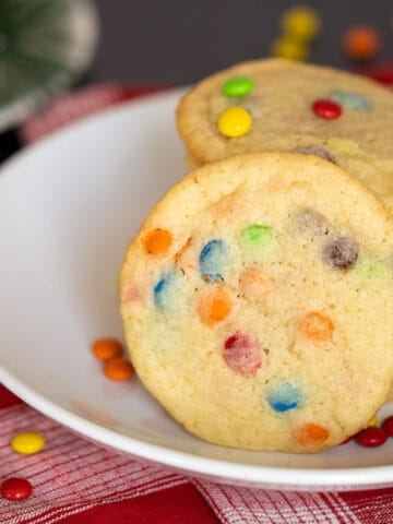 2021 New Year's cookie, on a white plate with colored mini M&M's all over the place.