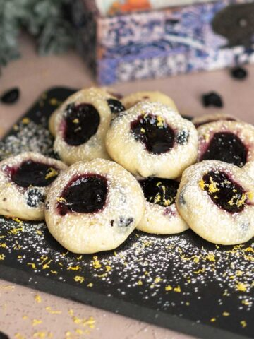 Blueberry with blueberry jam cookies on a black square serving plate with powdered sugar on top.