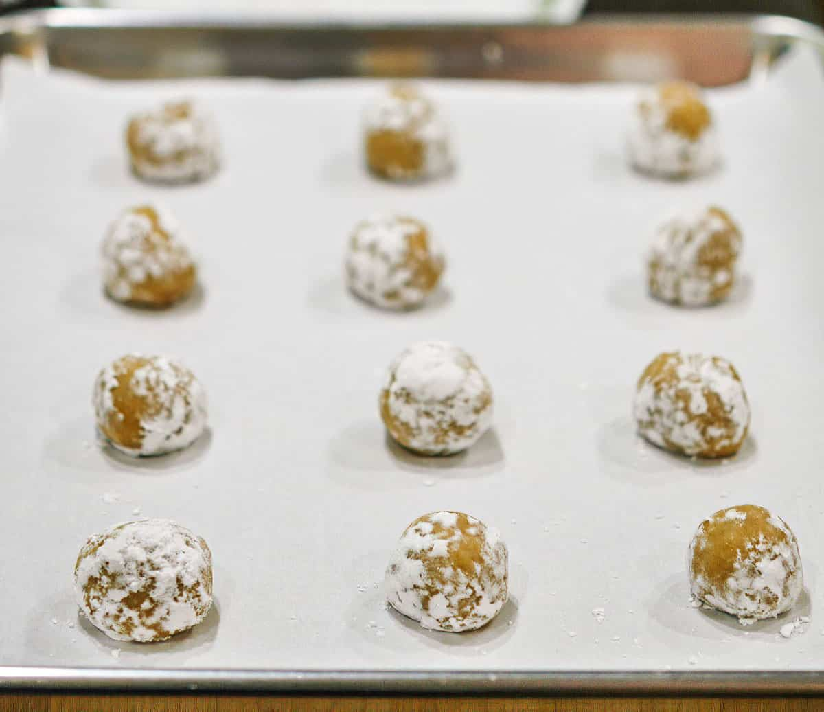 Brown butter crinkle cookie dough after being rolled in powder sugar and placed on a cookie sheet pan.
