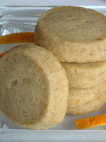 Stack of Cardamom Orange shortbread cookies with slices of orange skin.