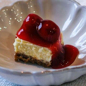 Cherry cheesecake bite in a white dish.