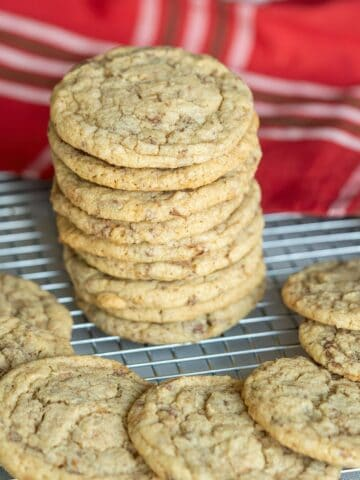 Chocolate English Toffee Bit Cookies are stacked and on display with a red cloth behind them.