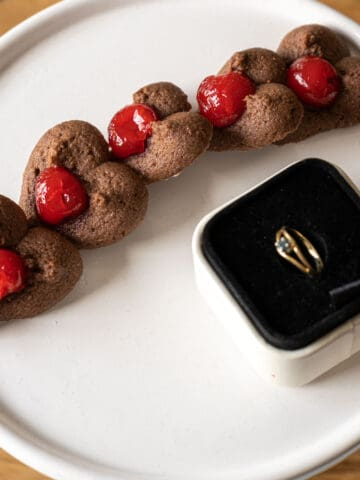 Chocolate spritz heart-shaped cookies with cherries on a white plate with a ring for Valentine's Day.