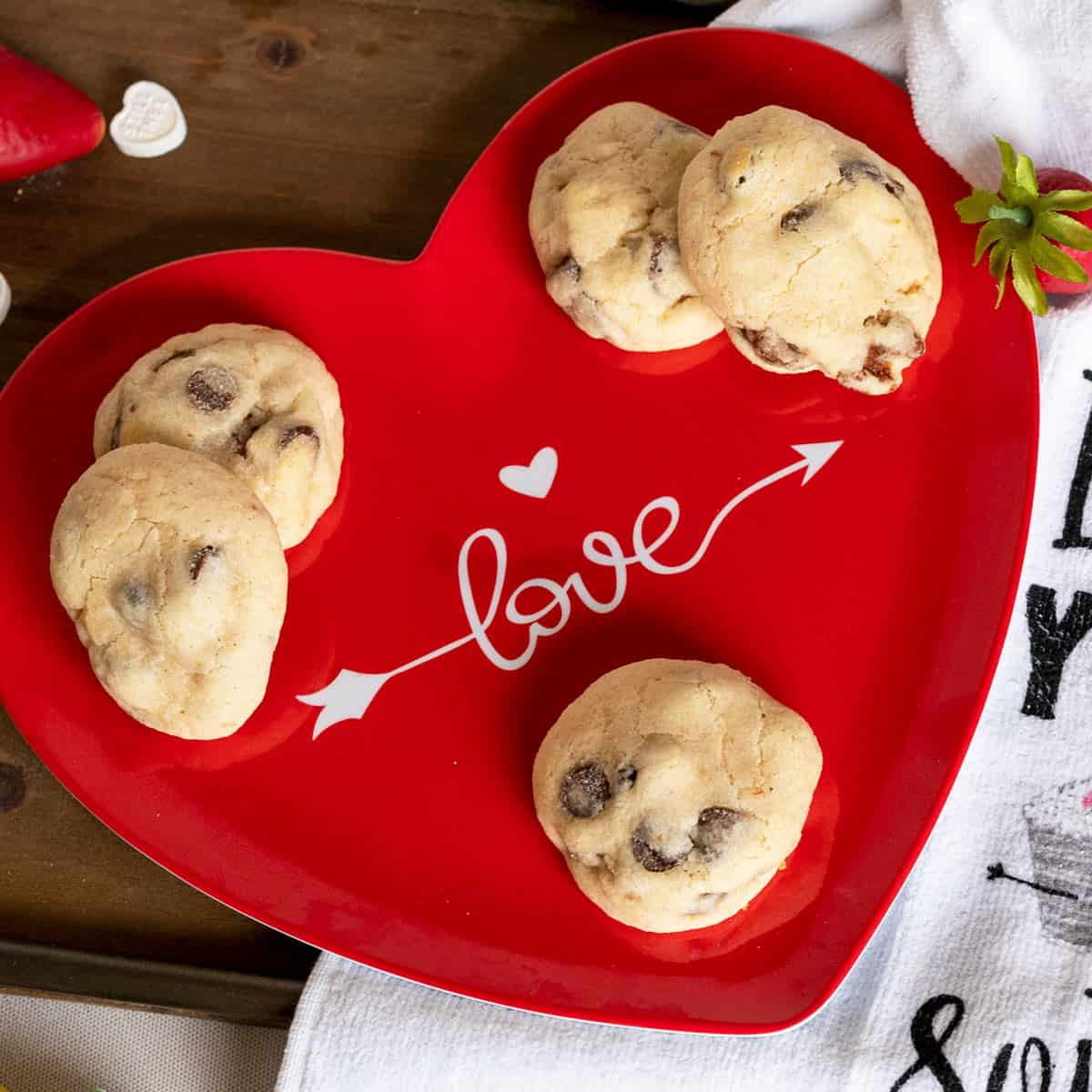 Chocolate chip and strawberry cookies sitting on a red plate with Love written across it for Valentine's Day.