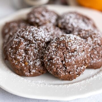 Chocolate Cookies with Orange and Toffee Bits with powdered sugar on top sitting on a white plate.