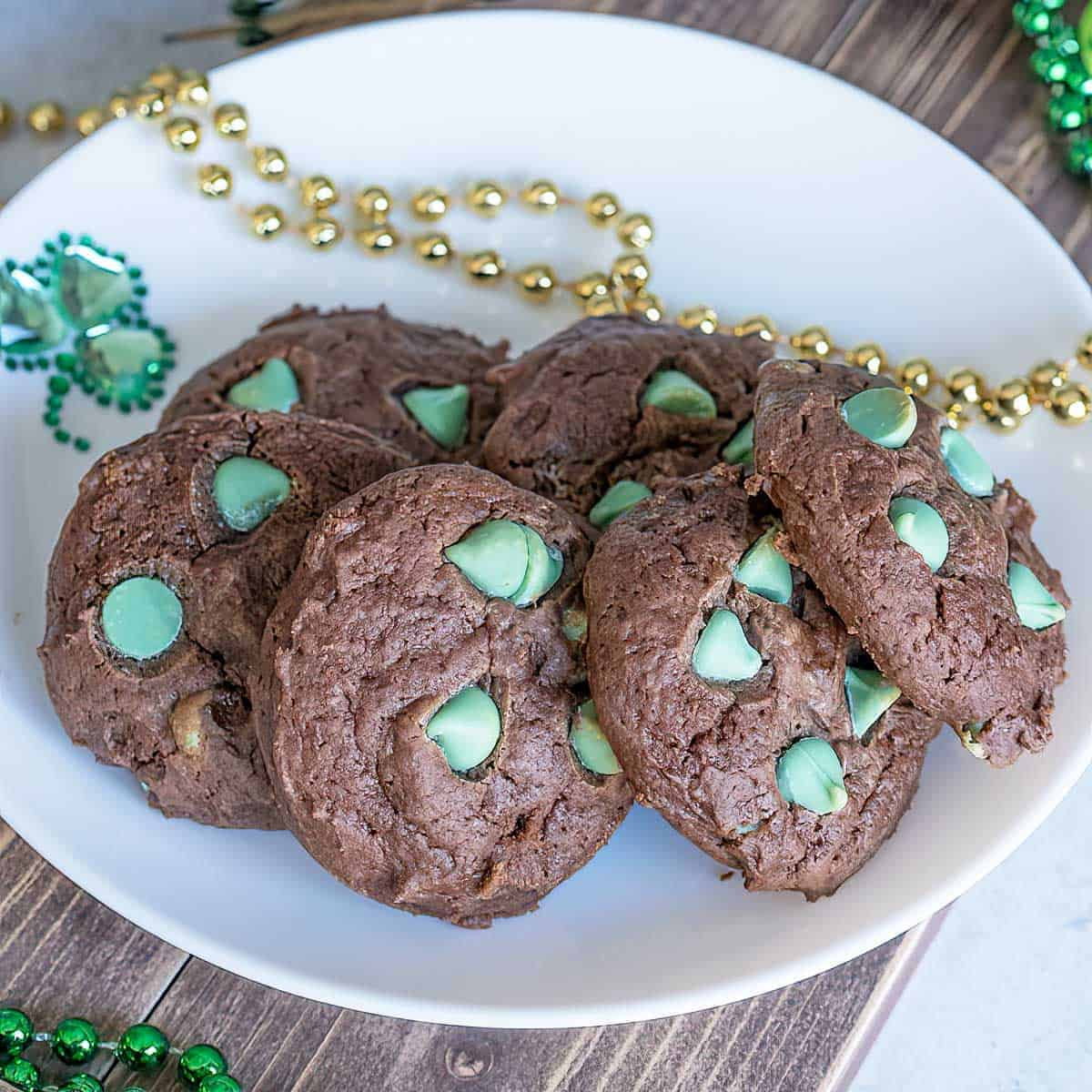 Chocolate mint cream cheese cookies sitting on a white plate with gold and green bead for decoration.