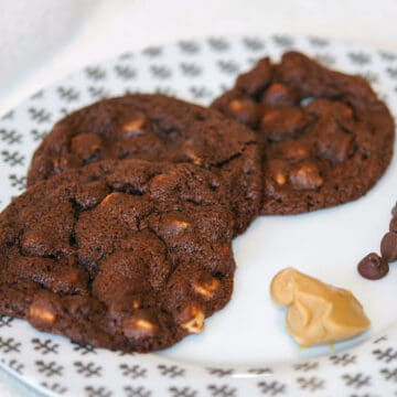Chocolate Peanut Butter Chip cookies on a white plate with a scoop of peanut butter and a few chocolate chips.