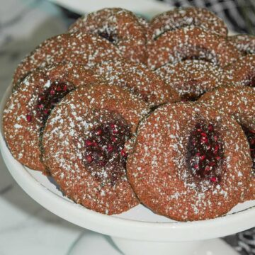 Chocolate with raspberry jam displayed on a white round platter stand.