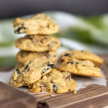 Chunky chocolate with cherry and pecan cookies stacked on a wooden tray.