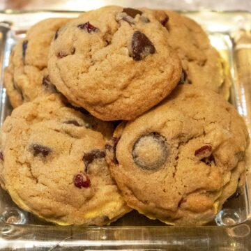 Cranberry and bittersweet chocolate chip cookies on a glass dish.