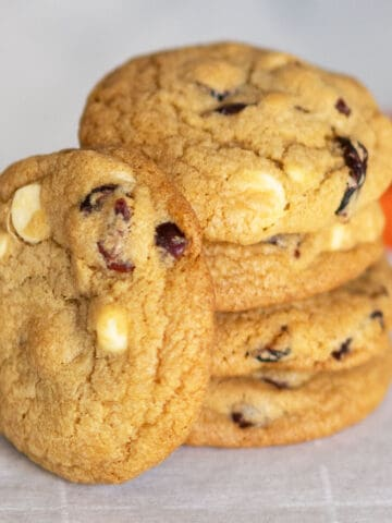 Stack of cranberry and white chocolate round cookies on a piece of parchment paper.