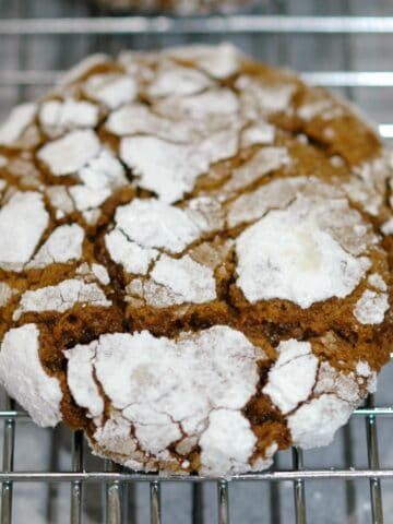 Gingerbread crinkle cookie finished and sitting on a wire rack.