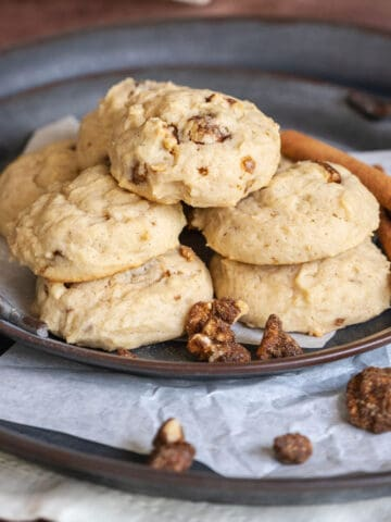 Glazed Maple Walnut cookies on parchment paper on top of a metal plate.