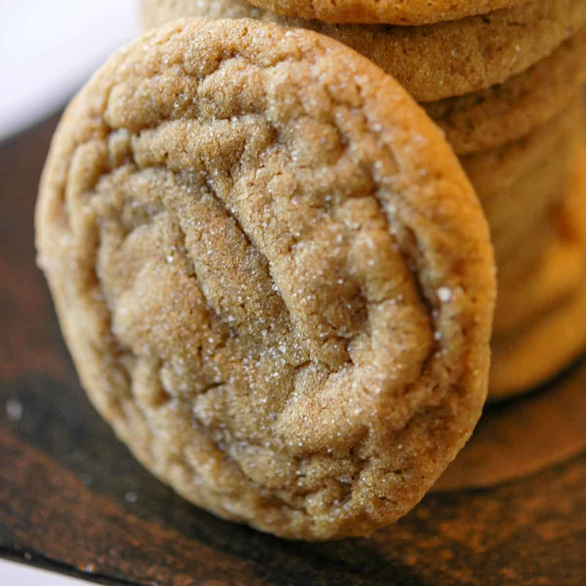 So good ginger cookie leaning against a stack of cookies, you can see the sugar baked onto the cookie.