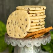 Chocolate Chip Sugar cookies stacked on a metal dish with two sticks of cinnamon on the side.