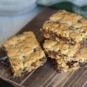 Four cookie bars stacked on a wooden plank.