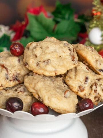 Cranberry Cinnamon Caramelized Walnut cookies on a white dish with fresh cranberries around the rim of the plate.