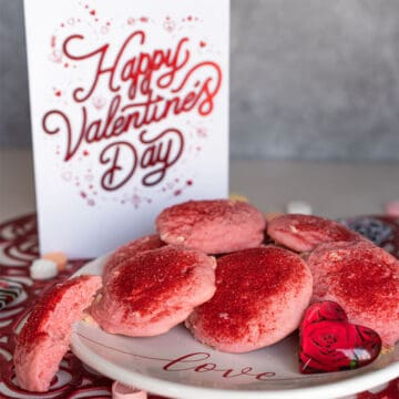 A pink and red strawberry and cream with white chocolate Valentine's Day Cookie on a white plate.