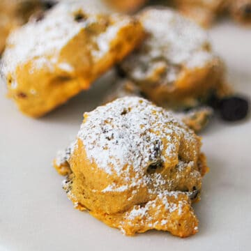 Hazelnut pumpkin cookies with powdered sugar on top sitting on parchment paper.