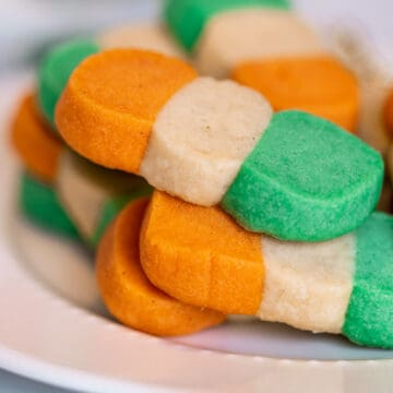 Irish-colored flag shortbread cookies on a white plate. Cookies are orange, white, and green.