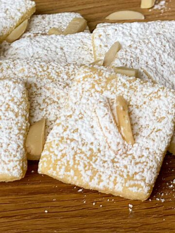 Italian Almond with Lemon cookies sitting on a wooden serving tray.