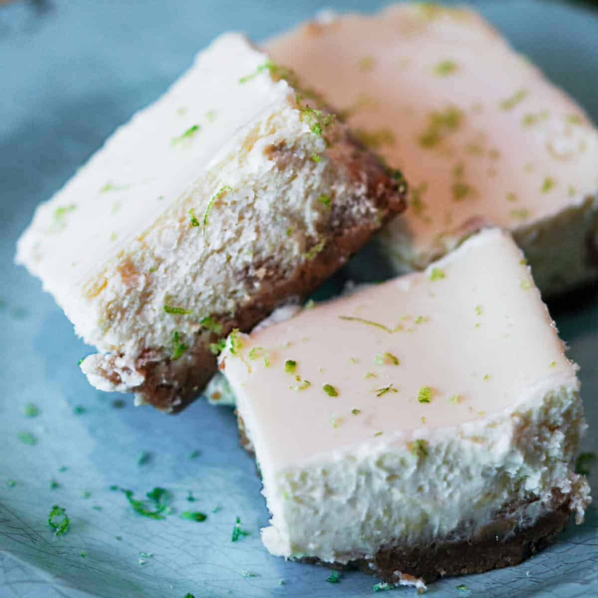 Key lime Cheesecake bars with flacks of lime zest on a blue plate.