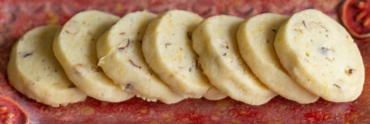 Lemon Ginger with Hazelnut Shortbread cookies in a line on a red dish.