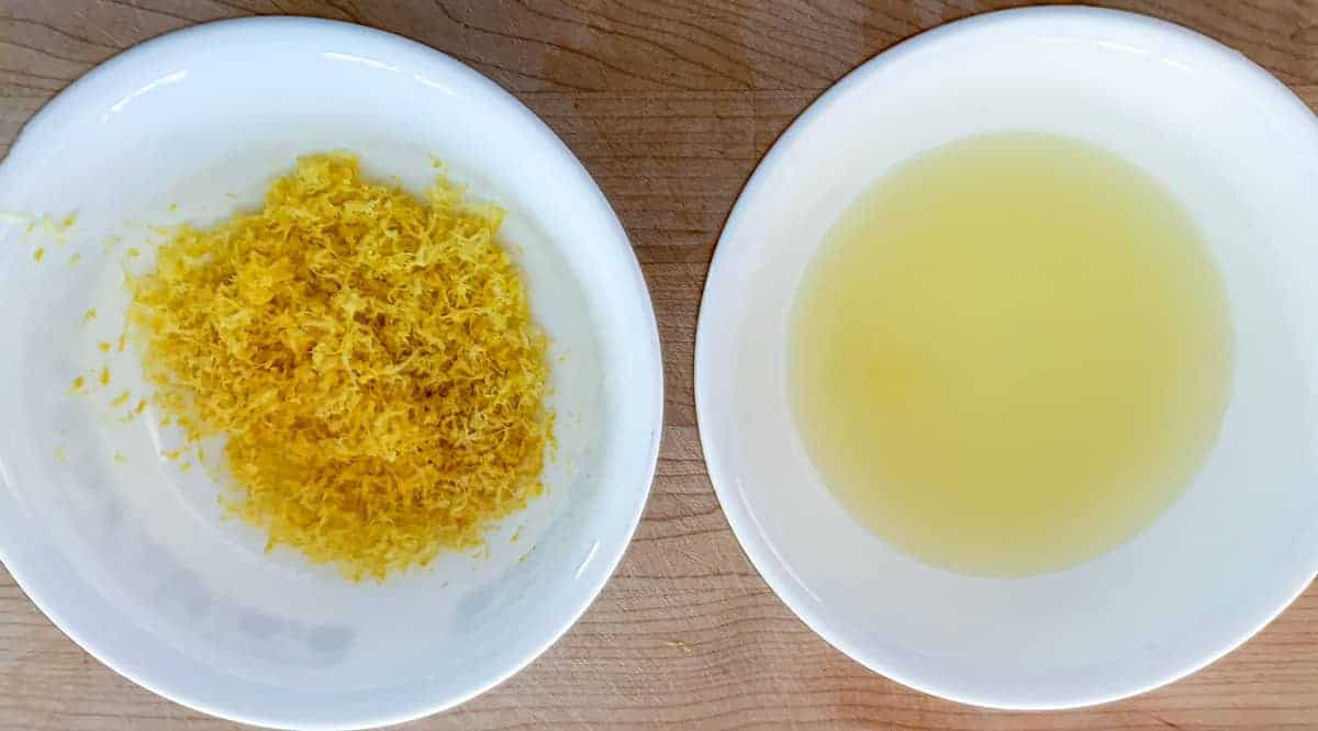 Lemon juice in one white bowl and lemon zest in another white bowl.