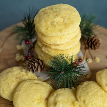 Lemon with a touch of Honey Cookies stacked with pine cone and pine branches around the base of cookies.