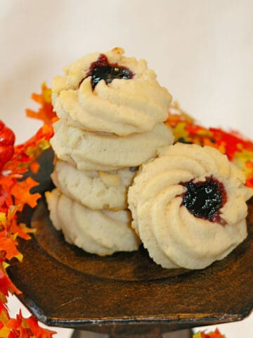 Shortbread cookie with jam with fall leaves around a stack of baked shortbread cookies with jam.