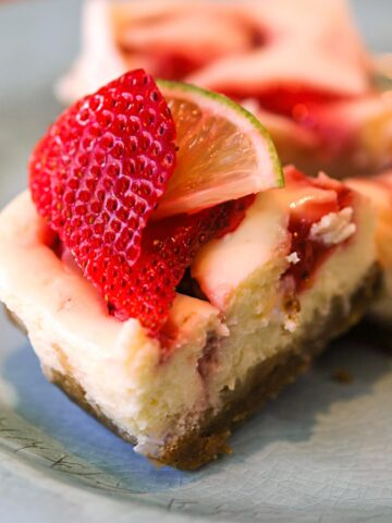 A piece of Strawberry Key Lime Cheesecake with a fresh piece of strawberry and key lime on top.