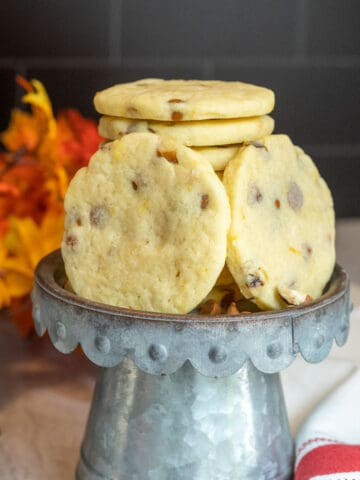 Finished Sugar Cookies with Cinnamon Chips and Orange cookies in a stack on a metal pedestal.
