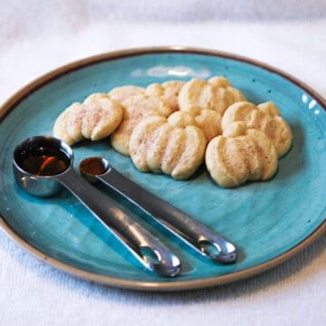 Maple Cinnamon Spritz Cookie on a blue plate with a spoon of cinnamon and a spoon of maple syrup.