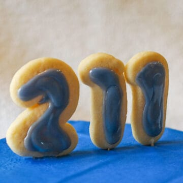 Cookies in the shape of 211 for the National 211 Day with blue icing which is their color and sitting on a blue platform.