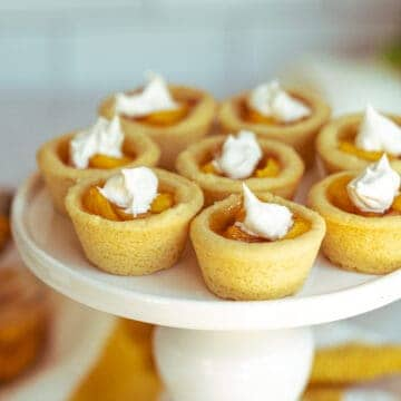 Peach Pie Cookie Cups with a dab of whip cream on top on a round pedestal serving dish.