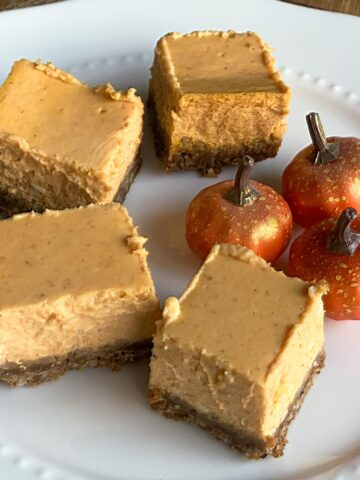 Pumpkin cheesecake squares on a white plate.